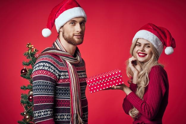 Casal jovem, decorações de natal, férias, posando com fundo vermelho.
