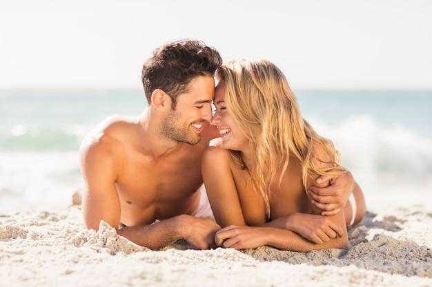 Casal jovem deitada na areia