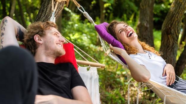 Casal jovem deitado em redes olhando um para o outro sorrindo