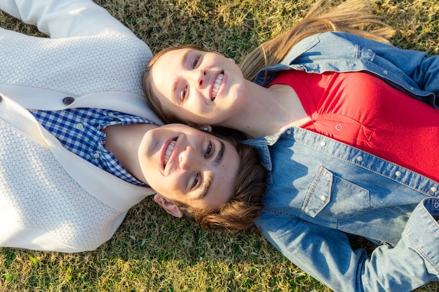 Casal jovem deitado na grama ao ar livre
