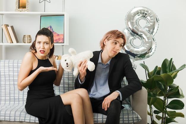 Casal jovem descontente no dia da mulher feliz com o ursinho de pelúcia sentado no sofá da sala de estar