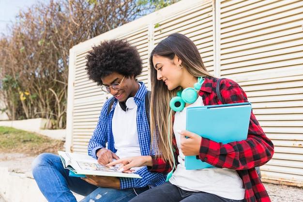 Casal jovem diverso estudando juntos no parque
