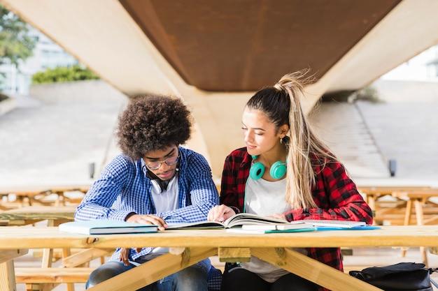 Casal jovem diverso sentado no banco de madeira, estudando juntos no campus da universidade