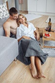 Casal jovem e adorável e feliz tomando café da manhã sentado perto do sofá com morango vermelho
