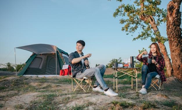 Casal jovem e alegre de mochileiros sentado em frente a uma barraca na floresta com um conjunto de café e fazendo um moedor de café fresco durante o acampamento nas férias de verão