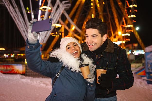 Casal jovem e alegre e feliz se divertindo à noite no parque de patinação no gelo, segurando xícaras de café para viagem, tirando uma selfie