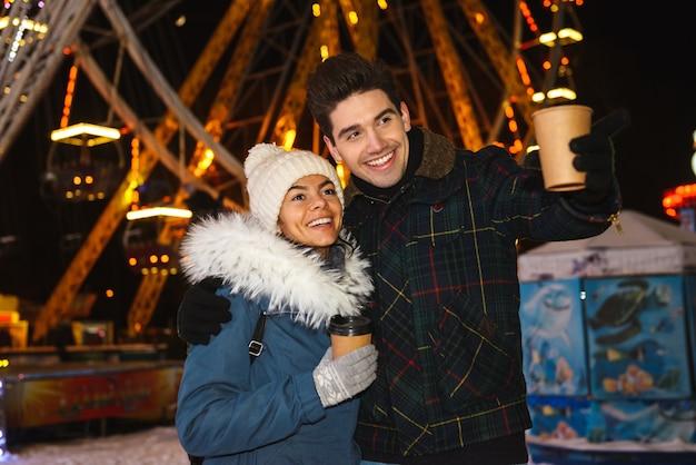 Casal jovem e alegre e feliz se divertindo no parque de patinação no gelo à noite, segurando xícaras de café para viagem
