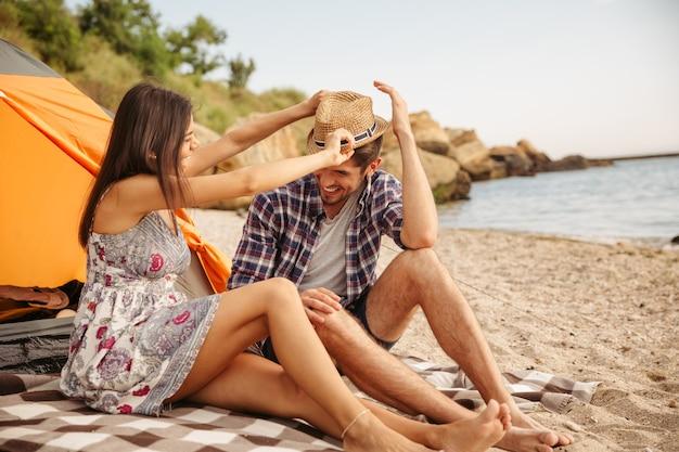 Casal jovem e alegre se divertindo acampando na praia