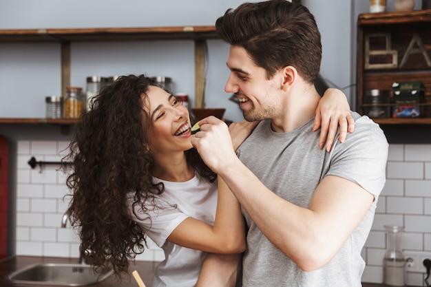 Casal jovem e animado cozinhando enquanto está sentado na cozinha, alimentando um ao outro