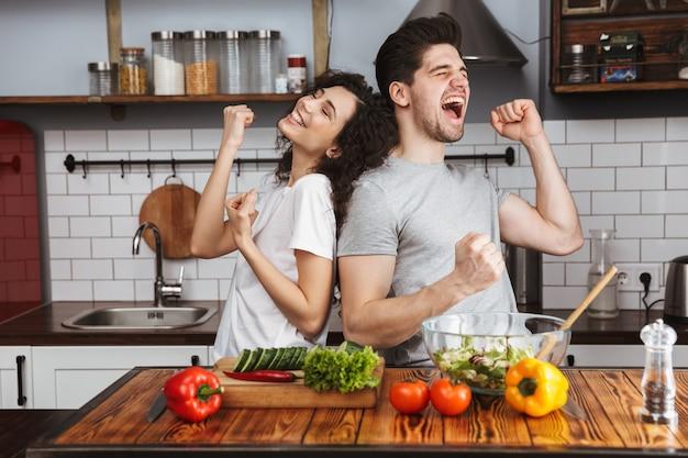 Casal jovem e animado cozinhando uma salada saudável enquanto está sentado na cozinha, cantando