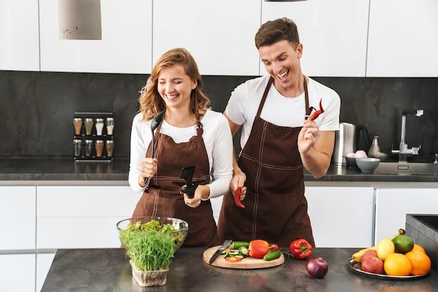 Casal jovem e atraente alegre usando avental, em pé na mesa da cozinha, cozinhando uma salada fresca e saudável, dançando, cantando