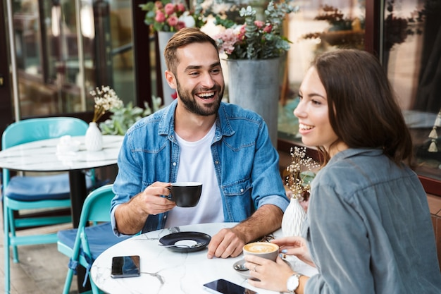 Casal jovem e atraente apaixonado almoçando enquanto está sentado à mesa do café ao ar livre, bebendo café, conversando