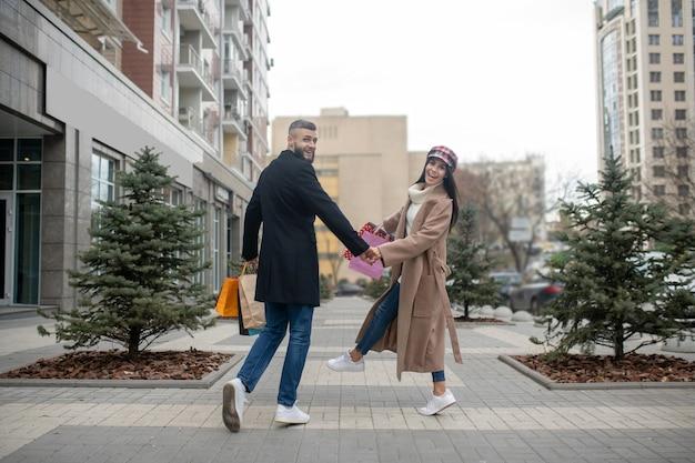Casal jovem e atraente caminhando com suas sacolas de compras enquanto faz compras
