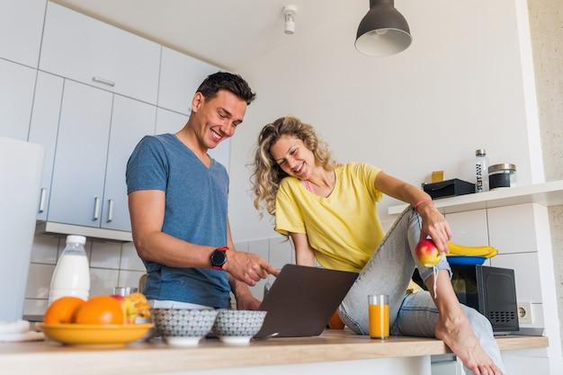 Casal jovem e atraente de um homem e uma mulher cozinhando o café da manhã na cozinha ficam juntos em casa sozinhos
