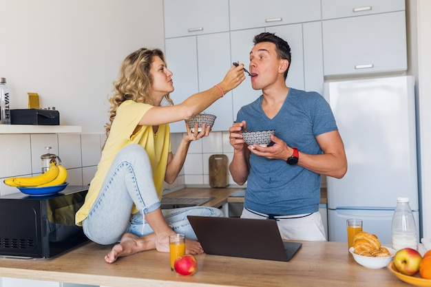 Casal jovem e atraente de um homem e uma mulher ficam em casa sozinhos tomando café da manhã na cozinha
