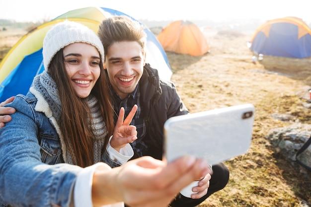 Casal jovem e atraente descansando sentado na barraca ao ar livre, segurando uma xícara e uma garrafa térmica, tirando uma selfie