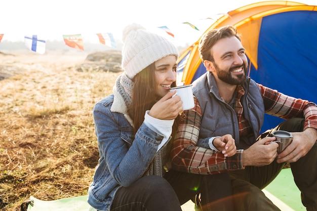 Casal jovem e atraente descansando sentado na barraca ao ar livre, segurando uma xícara e uma garrafa térmica
