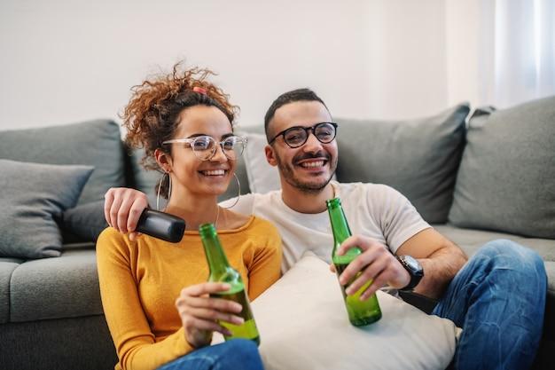 Casal jovem e atraente sentado em casa, bebendo cerveja e assistindo televisão
