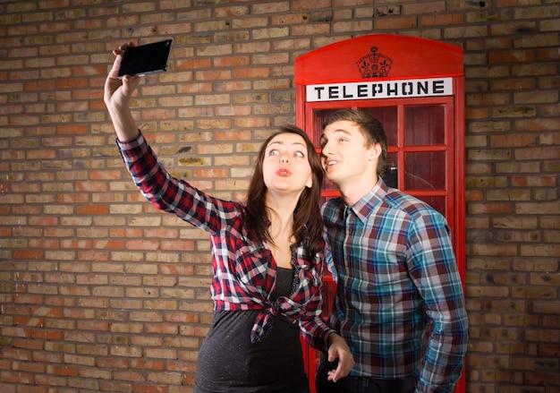 Casal jovem e atraente tirando uma selfie no celular e posando com uma icônica cabine telefônica britânica vermelha atrás deles contra uma parede de tijolos
