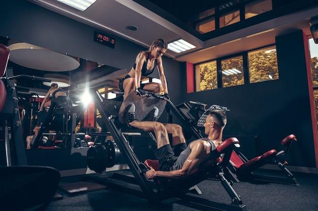 Casal jovem e bonita fazendo exercícios na academia juntos. homem branco treinando com a treinadora