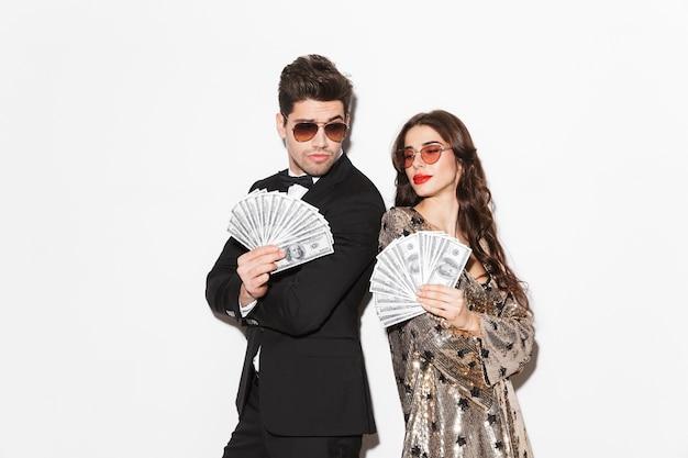 Casal jovem e bonito, bem vestido, isolado sobre o vermelho, mostrando notas de dinheiro