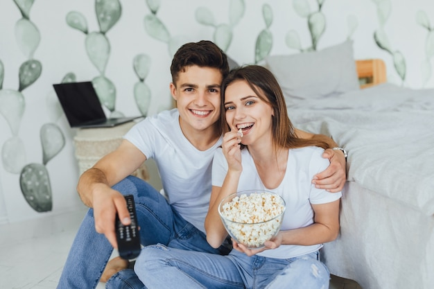 Casal jovem e bonito com roupas casuais assistindo tv em casa na cabeceira da cama e comendo pipoca