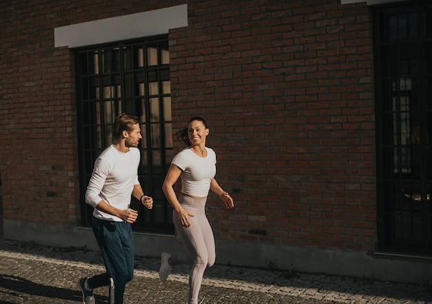 Casal jovem e bonito correndo no ambiente urbano