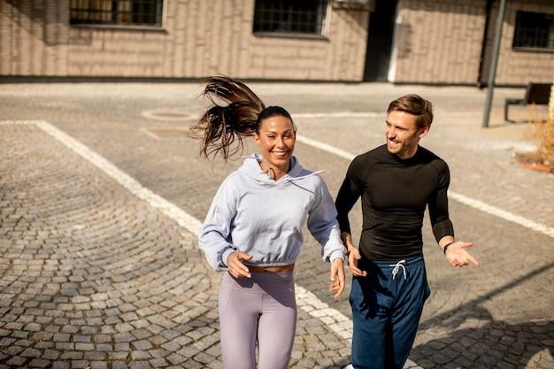 Casal jovem e bonito de fitness correndo em área urbana