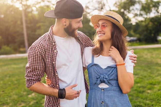 Casal jovem e bonito de hipster caminhando no parque, amigos se divertindo juntos, romance num encontro, estilo de moda de verão, roupas coloridas de hipster, homem e mulher sorrindo se abraçando