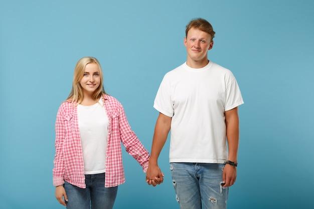 Casal jovem e bonito, dois amigos, cara e mulher em camisetas brancas vazias em branco rosa posando
