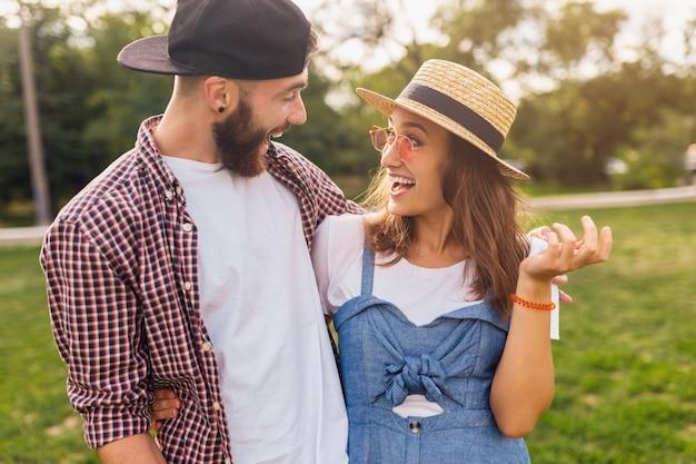 Casal jovem e bonito hippie andando no parque conversando, rindo, amigos se divertindo juntos, romance num encontro, estilo de moda de verão, roupas coloridas hipster, homem e mulher sorrindo se abraçando