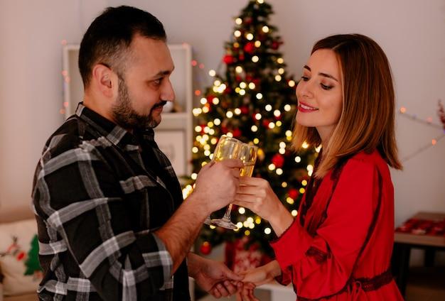 Casal jovem e bonito, homem e mulher com taças de champanhe tilintando de taças, celebrando o natal juntos em um quarto decorado com uma árvore de natal ao fundo
