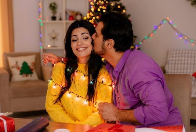 Casal jovem e bonito, homem e mulher, sentados à mesa com o homem guirlanda beijando sua namorada em um quarto decorado de natal com árvore de natal na parede