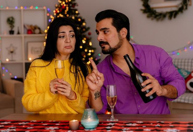 Casal jovem e bonito, homem e mulher sentados à mesa com taças de champanhe, celebrando o natal juntos na sala decorada com árvore de natal na parede