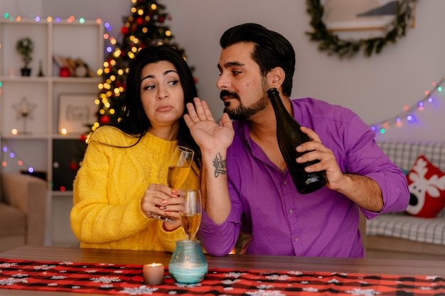 Casal jovem e bonito, homem e mulher sentados à mesa com taças de champanhe, felizes apaixonados, celebrando o natal juntos na sala decorada de natal com uma árvore de natal ao fundo