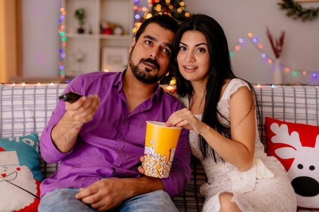 Casal jovem e bonito, mulher feliz e homem sentado em um sofá com balde de pipoca assistindo tv juntos em um quarto decorado com árvore de natal ao fundo