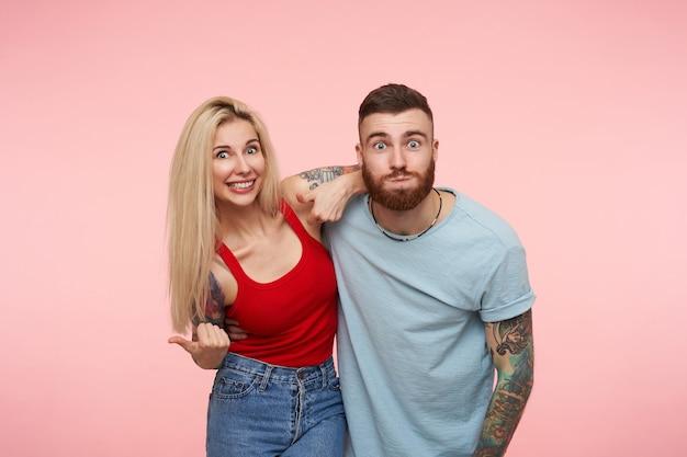 Casal jovem e bonito positivo com tatuagens se abraçando enquanto faz uma careta e parece animado, de pé na rosa