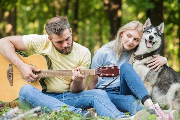 Casal jovem e bonito relaxando na natureza com um cachorro tocando violão