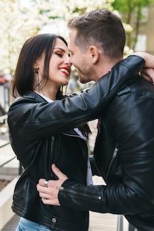 Casal jovem e bonito vestindo jaquetas de couro durante um encontro na rua