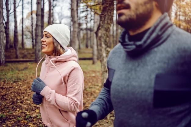 Casal jovem e dedicado e esportivo em roupas esportivas, correndo na natureza lado a lado no tempo frio.