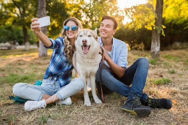 Casal jovem e elegante brincando com um cachorro no parque