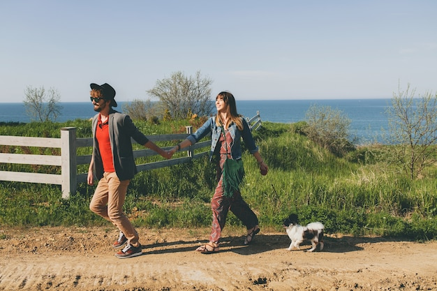 Casal jovem e elegante hippie apaixonado andando com o cachorro no campo, correndo, se divertindo