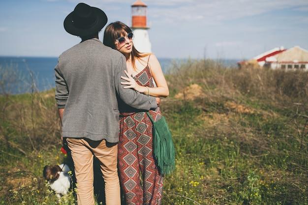 Casal jovem e elegante hippie apaixonado, caminhando com um cachorro no campo