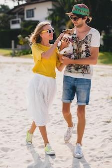 Casal jovem e elegante moderno apaixonado andando brincando de cachorro cachorrinho jack russell na praia tropical, areia branca, clima romântico, se divertindo, ensolarado, homem mulher juntos, férias