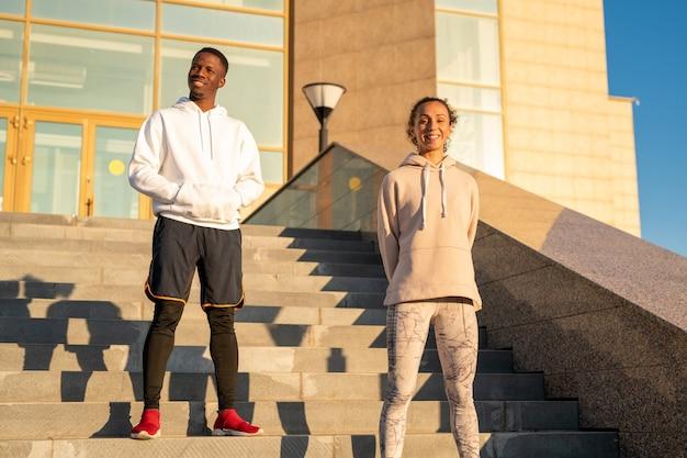 Casal jovem e esportivo intercultural feliz em roupas esportivas em pé contra uma escada e arquitetura moderna em ambiente urbano