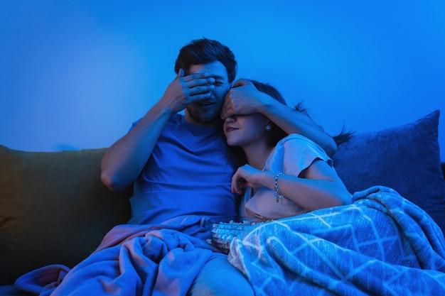 Casal jovem e feliz assistindo filme de terror em casa