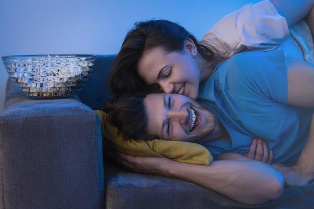 Casal jovem e feliz assistindo programa de comédia na tv em casa