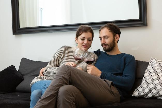 Casal jovem e feliz bebendo vinho e relaxando em casa