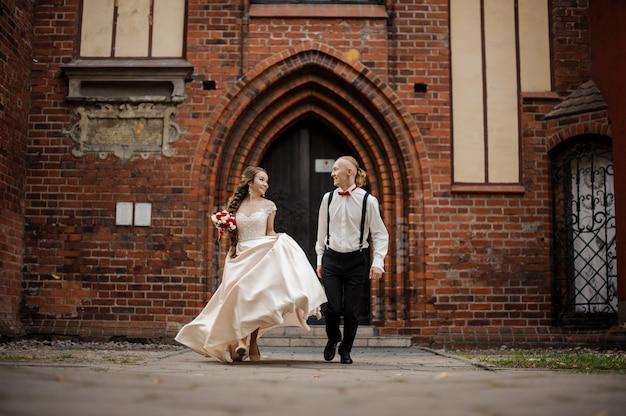 Casal jovem e feliz caminhando em um jardim de um prédio antigo de tijolos vermelhos com arco