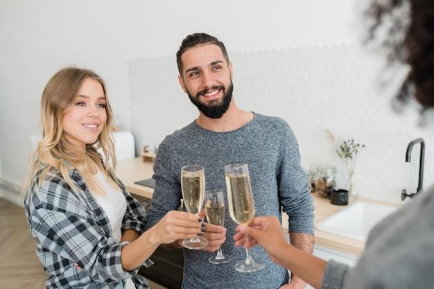 Casal jovem e feliz com taças de champanhe brindando com um dos amigos em uma festa em casa